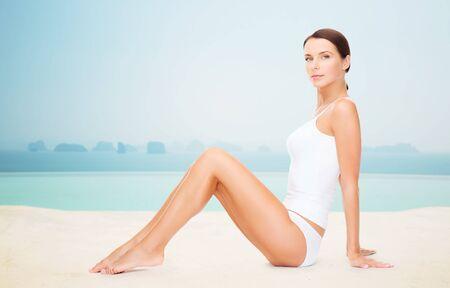 personas, belleza, spa y resort concepto - mujer hermosa en ropa interior de algodón sobre el infinito piscina de borde de fondo