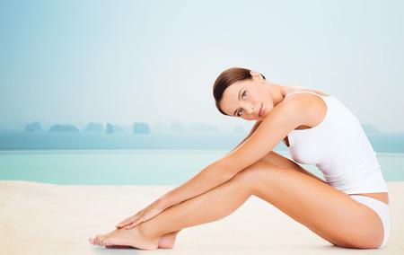 cuerpo perfecto femenino: personas, belleza, spa y resort concepto - mujer hermosa en ropa interior de algodón tocando sus piernas sobre el infinito piscina de borde de fondo
