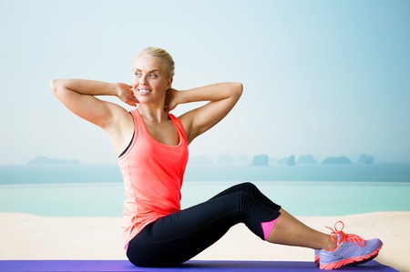 situp: fitness, sport, exercising and people concept - smiling woman doing sit-up on mat over sea and pool at hotel resort background Stock Photo