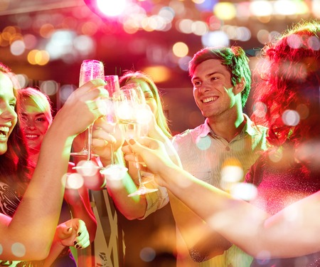 sparkling wine: party, holidays, celebration, nightlife and people concept - smiling friends clinking glasses of champagne in club