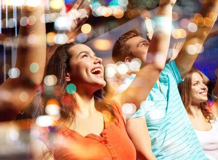 gente saludando: fiesta, d�as de fiesta, celebraci�n, vida nocturna y la gente concepto - amigos sonrientes que agitan las manos en el concierto en el club