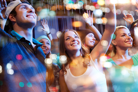 concert crowd: party, holidays, music events, nightlife and people concept - group of happy friends at hip-hop concert in night club Stock Photo