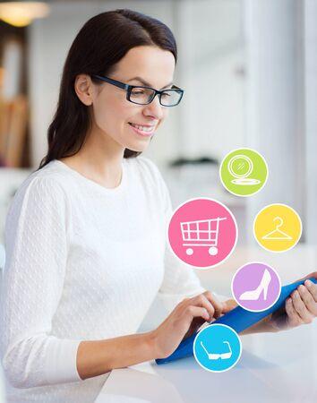 mujeres felices: la gente, las compras en l�nea, la tecnolog�a y el concepto de estilo de vida - sonriente joven con tablet pc ordenador e internet iconos en la oficina o en el hogar Foto de archivo