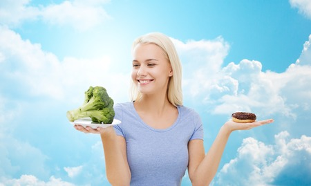 good looking woman: healthy eating, junk food, diet and choice people concept - smiling woman choosing between broccoli and donut over blue sky and clouds background