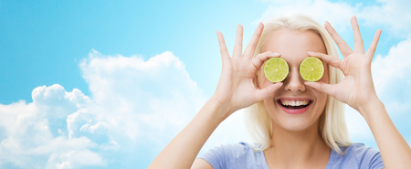 fruit background: healthy eating, organic food, fruit diet, comic and people concept - happy woman having fun and covering her eyes with lime slices over blue sky and clouds background