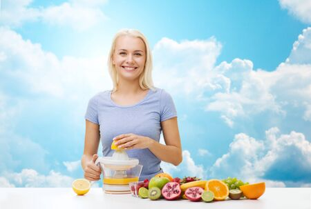juice squeezer: healthy eating, vegetarian food, diet, detox and people concept - smiling woman with squeezer squeezing fruit juice over blue sky and clouds background