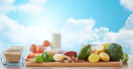 food still: balanced diet, cooking, culinary and food concept - close up of vegetables, fruits and meat on wooden table over blue sky and clouds background