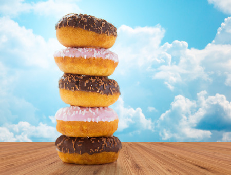 junk: food, junk-food and eating concept - close up of glazed donuts pile on wooden table over blue sky and clouds background Stock Photo