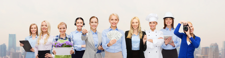 people, profession, employment, compensation and finances concept - happy businesswoman holding dollar money with group of professional workers over city background