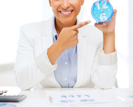 office time: business, office, time, deadline concept - attractive businesswoman pointing at clock