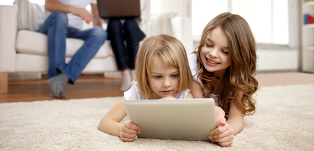 family playing: people, family, technology and children concept - happy little girls playing with tablet pc computer at home Stock Photo