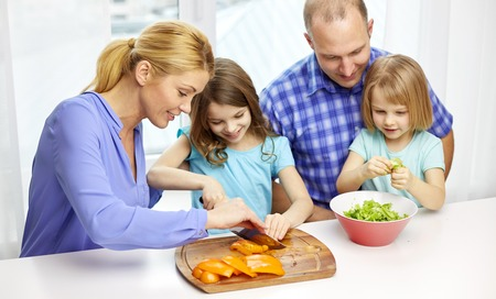 family together: food, children, culinary and people concept - happy family with two kids cooking vegetables at home