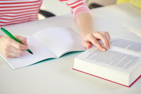 personas y concepto de la educación - Cierre de manos femeninas con el libro o libro de texto escrito al bloc de notas en la escuela