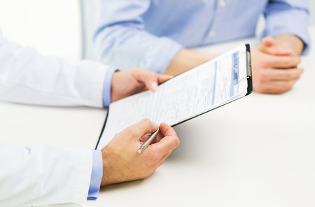 medicine, health care, people and prostate cancer concept - close up of f male doctor and patient hands with clipboard Stock Photo