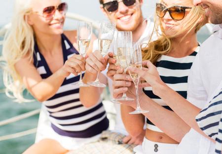 Urlaub, Reisen, Meer, Urlaub und Menschen Konzept - Nahaufnahme von glückliche Freunde Gläser Champagner und Segeln auf Yacht Klirren