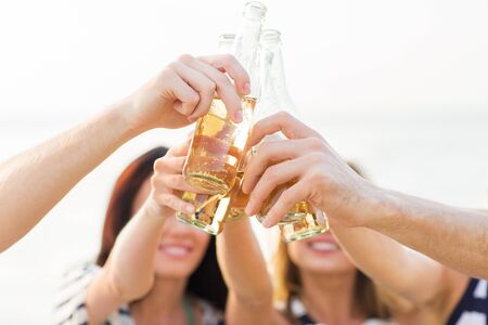 vacation, celebration, holidays and people concept - close up of happy friends clinking bottles with drinks at party