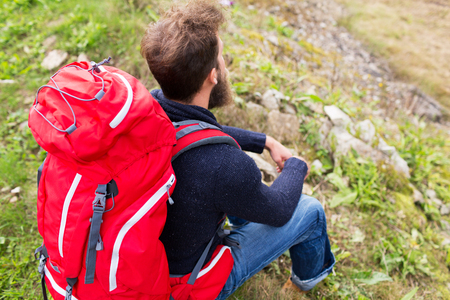 sitting on the ground: adventure, travel, tourism, hike and people concept - man hiker with red backpack sitting on ground Stock Photo