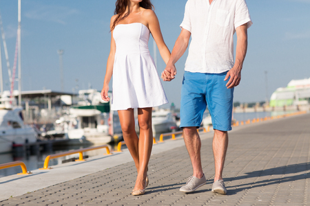 waterfront: love, travel, tourism, summer and people concept - close up of couple holding hands and walking along waterfront