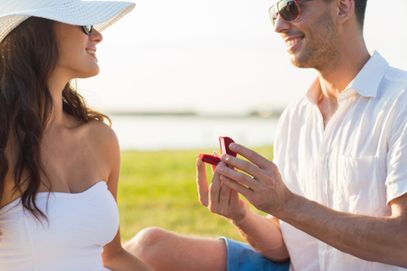 marry me: love, proposal, people and holidays concept - happy couple with engagement ring in little red gift box Stock Photo