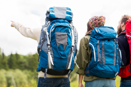 backpacks: adventure, travel, tourism, hike and people concept - group of friends walking with backpacks from back