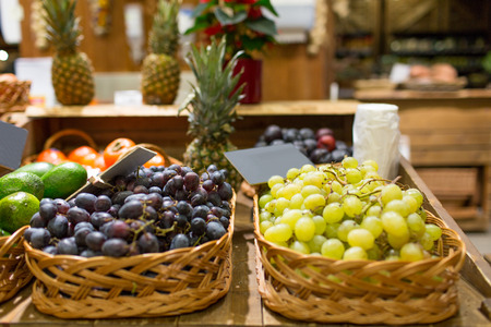 baskets: sale, shopping and eco food concept - ripe red and white grape in baskets with nameplates at grocery market Stock Photo