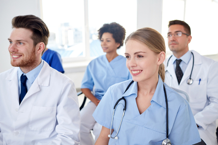 health education: profession, medical education, health care, people and medicine concept - group of happy doctors on seminar in lecture hall at hospital