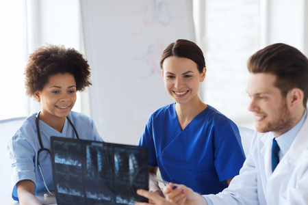 image: radiology, people and medicine concept - group of happy doctors looking to and discussing x-ray image at hospital Stock Photo