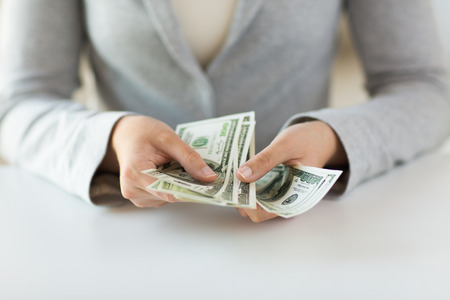 business, finance, saving, banking and people concept - close up of woman hands counting us dollar money Stock Photo