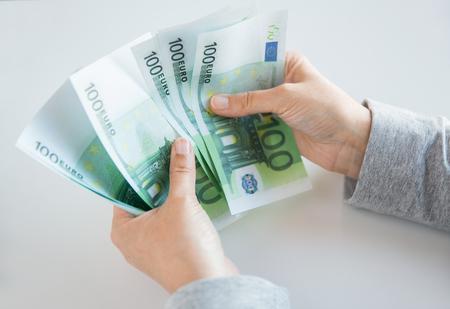 dinero euros: negocios, las finanzas, el ahorro, la banca y las personas concepto - cerca de la mujer en las manos contando el dinero del euro