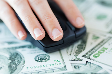 mice: business, finance, internet earning and people concept - close up of hand with computer mouse on money