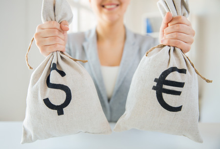 american banker: business, finance, saving, banking and people concept - close up of woman hands holding dollar and euro money bags Stock Photo