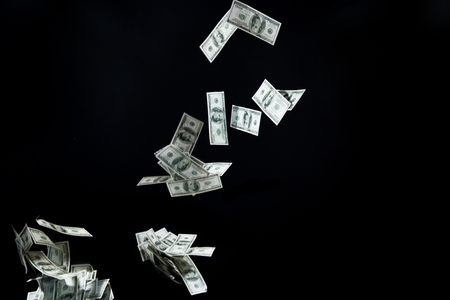 business, finance, waste and concept - close up of us dollar money flying over black background