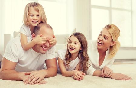 donna innamorata: famiglia, bambini e concetto di casa - famiglia sorridente con e due bambine che si trovano sul pavimento a casa e divertirsi