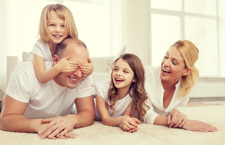 making love: family, children and home concept - smiling family with and two little girls lying on floor at home and having fun