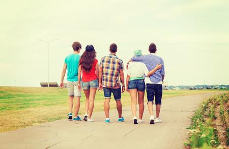 pareja adolescente: días de fiesta, vacaciones, el amor y el concepto de amistad - grupo de adolescentes caminar al aire libre de la parte posterior