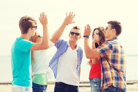five people: friendship, leisure, summer, gesture and people concept - group of smiling friends making high five outdoors