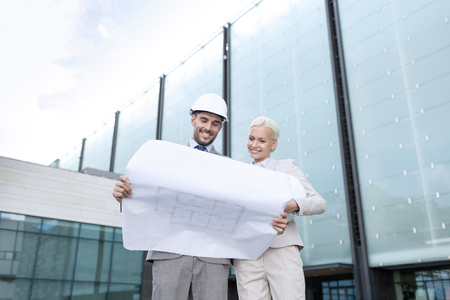 unwrapping: business, partnership, architecture and people concept - smiling businessman and businesswoman with blueprint and helmets on city street