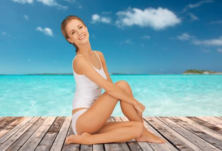jungen unterwäsche: Wellness, Gesundheit und Menschen Konzept - schöne junge Frau in Unterwäsche aus Baumwolle auf Holzboden über dem Meer und blauen Himmel im Hintergrund sitzt
