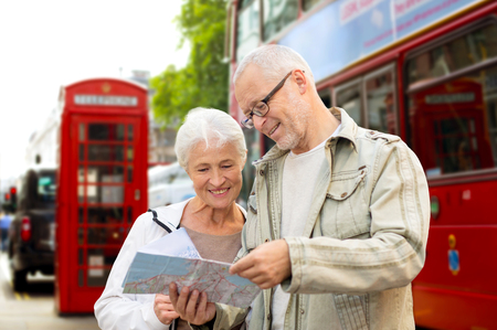 family, age, tourism, travel and people concept - senior couple with map over london city street background Stok Fotoğraf