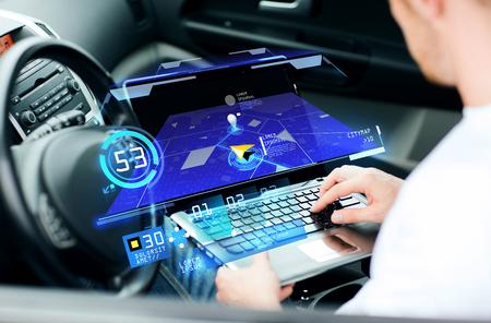 Transporte, tecnología moderna y concepto de personas - hombre usando el sistema de navegación en la computadora portátil en el coche Foto de archivo