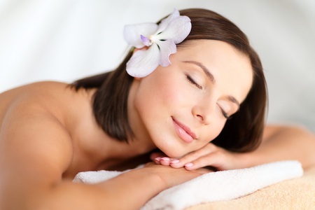 beauty resort: health, beauty, resort and relaxation concept - beautiful woman with flower in her hair in spa salon lying on the massage desk