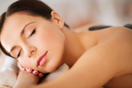 beauty resort: health and beauty, resort and relaxation concept - beautiful woman with closed eyes in spa salon with hot stones