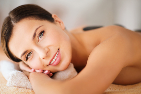 beauty resort: health and beauty, resort and relaxation concept - beautiful woman in spa salon with hot stones