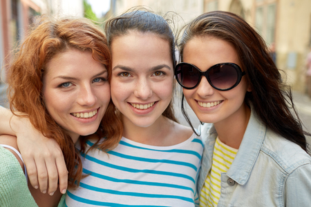 vacation, weekend, leisure and friendship concept - smiling happy young women or teenage girls on city street Standard-Bild