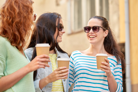 disposable: vacation, weekend, takeaway drinks, leisure and friendship concept - smiling happy young women or teenage girls drinking coffee from disposable paper cups on city street Stock Photo