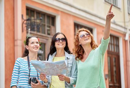 Turismo, viaggi, tempo libero, vacanze e concetto di amicizia - sorridente adolescenti con mappa e fotocamera all'aperto Archivio Fotografico - 57179605