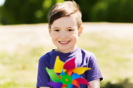 5 6 years: summer, childhood, leisure and people concept - happy little boy with colorful pinwheel toy outdoors Stock Photo
