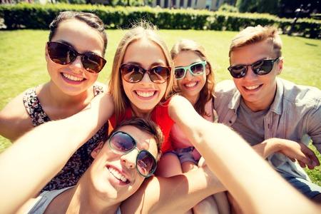 amistad, ocio, verano, la tecnología y el concepto de la gente - grupo de amigos sonrientes que hacen autofoto con el teléfono inteligente, cámara o Tablet PC en el parque