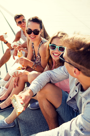 young group: friendship, leisure, summer and people concept - group of smiling friends in sunglasses sitting with food on city square