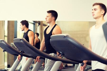 hombres haciendo ejercicio: deporte, fitness, estilo de vida, la tecnolog�a y el concepto de la gente - grupo de hombres que ejercitan en la cinta en el gimnasio